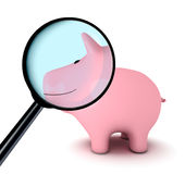 Smiley piggy bank under the magnifying glass Stock Photo
