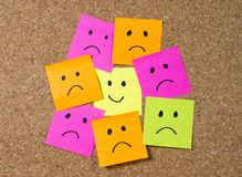 Smiley post it note on corkboard in happiness versus depression concept. Smiley cartoon face expression on yellow post it note surrounded by sad and depressed Stock Photos