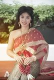 The pretty Thai lady in Middle Thai classical traditional dresses suit pose sitting hold garland in a park. The smiley pretty Thai lady in Middle Thai classical stock images