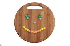 Smiley of the round chocolate candies on a wooden board Stock Images