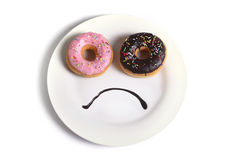 Smiley sad face made on dish with donuts as eyes and chocolate syrup mouth in sugar sweet addiction diet and nutrition. Smiley sad face worried about overweight Stock Photo