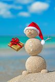 Smiley sandy snowman at beach in christmas hat with golden gift. Royalty Free Stock Images