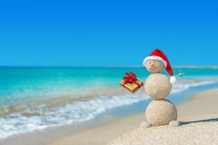 Smiley sandy snowman at beach in christmas hat with golden gift. Holiday concept for New Years Cards royalty free stock image