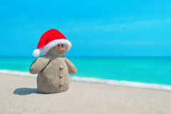 Smiley sandy Snowman in red Santa hat at sea beach Royalty Free Stock Photography