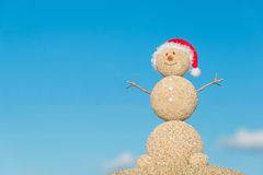 Smiley sandy snowman in santa hat. Holiday concept for New Years Stock Photos
