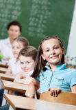 Smiley schoolgirl sits at the desk Stock Photo