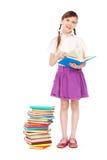 Smiley-Schulmädchen, das nahe Bücher steht Stockfotografie
