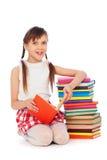 Smiley-Schulmädchen, das nahe Büchern sitzt Stockfotos