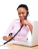 Smiley secretary talking on the phone. And writing Royalty Free Stock Photo