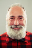 Smiley senior man with grey-haired beard over light grey backgro Royalty Free Stock Image