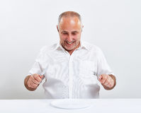 Smiley senior man holding fork with knife Royalty Free Stock Images