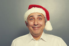 Smiley senior man in red santa hat Royalty Free Stock Images