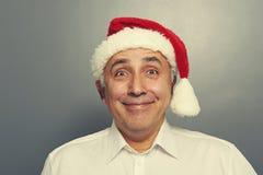 Smiley senior man in red santa hat Royalty Free Stock Images