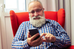 Smiley senior man with smartphone Royalty Free Stock Image