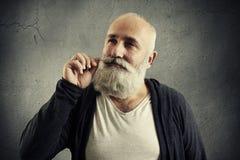 Smiley senior man twisting his mustache Royalty Free Stock Photos