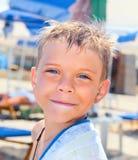 Smiley sete anos de menino idoso na praia imagem de stock royalty free