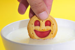 Smiley-shaped cookie in milk Stock Photo