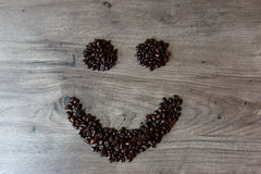 Smiley shaped figure made out of coffee beans on top of a table. Smiley shaped figure made out of coffee beans on top of a wooden table Royalty Free Stock Photos