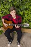 Smiley som är tonårig med den akustiska gitarren Royaltyfri Foto