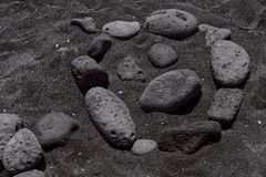 Smiley som läggas ut ur stenar på en svart strand på kanariefågelöarna royaltyfri fotografi