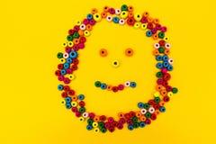 Smiley sonriente de los juguetes redondos multicolores en un fondo amarillo fotos de archivo libres de regalías