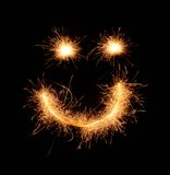 Smiley sorridente strano felice disegnato con le scintille su fondo nero Immagine Stock