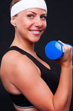 Smiley sportswoman with blue dumbbells Royalty Free Stock Photos