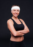 Smiley sportswoman over dark background Royalty Free Stock Image