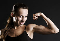 Smiley sportswoman showing her muscles Royalty Free Stock Photos