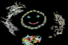 Smiley from Staples. On a black background with multicolored paper clips laid out smiley and other staples Royalty Free Stock Photography