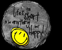 Be Happy. A yellow smiley face stone that says, Lifes too short to be anything but Happy Royalty Free Stock Photo