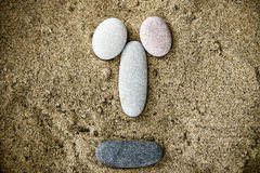 Smiley of stones on sand closeup Royalty Free Stock Photography