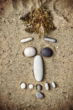 Smiley of stones on sand closeup Stock Images