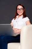 Smiley student in glasses with laptop. Sitting on chair Stock Photography