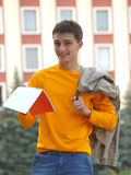 A smiley student with notebook. Cheerful student holding jacket and opened notebook Royalty Free Stock Images