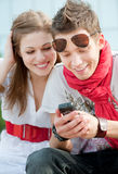 Smiley teenagers looking at cellphone. Attractive smiley teenagers looking at cellphone Royalty Free Stock Photography