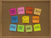 Smiley and ten positive emotions on bulletin board. Positive emotions concept - color sticky notes around smiley on cork bulletin board Royalty Free Stock Image