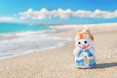 Smiley toy christmas snowman at hot sea beach. Stock Photos