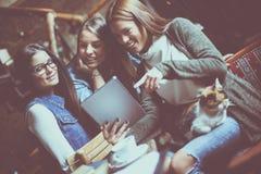 Smiley três estudantes no café usando a tabuleta e o hav digitais imagens de stock royalty free