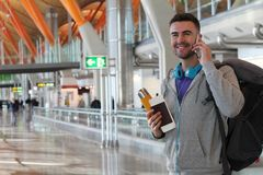 Smiley traveler calling from the airport.  Royalty Free Stock Photography