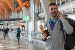 Smiley traveler calling from the airport.  Royalty Free Stock Images