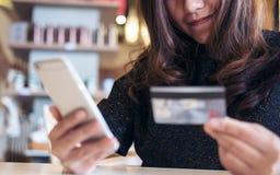 Smiley twarzy Azjatycka kobieta trzyma kredytową kartę i telefon komórkowego w biurze Obrazy Royalty Free