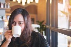 Smiley twarzy Azjatycka kobieta trzyma kredytową kartę i telefon komórkowego w biurze Fotografia Royalty Free