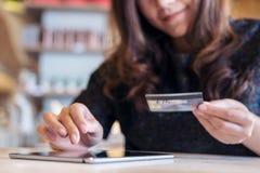 Smiley twarzy Azjatycka kobieta trzyma kredytową kartę i używa pastylka komputer osobistego w restauraci Obrazy Royalty Free