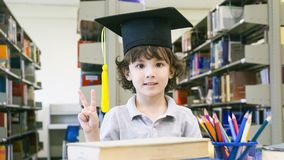 Smiley white boy with the Graduation cap and diploma paper stand stock photos