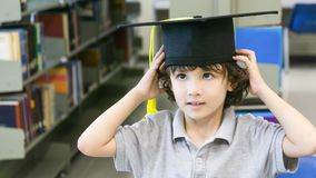 Smiley white boy with the Graduation cap and diploma paper stand. S and smile in the shelf of books background Stock Photography