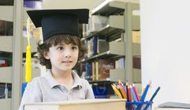 Smiley white boy with the Graduation cap and diploma paper stand. S and smile in the shelf of books background Royalty Free Stock Photography