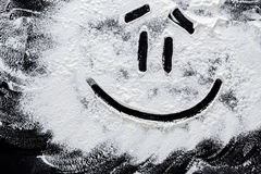 Smiley on white wheat flour at abstract black background. Top view on blackboard or table. Cooking dough or pastry Stock Images