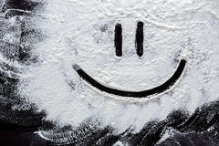 Smiley on white wheat flour at abstract black background. Top view on blackboard or table. Cooking dough or pastry Stock Photography