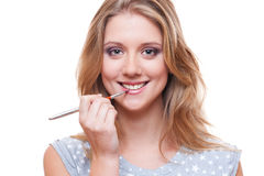 Smiley woman applying lipstick Royalty Free Stock Images